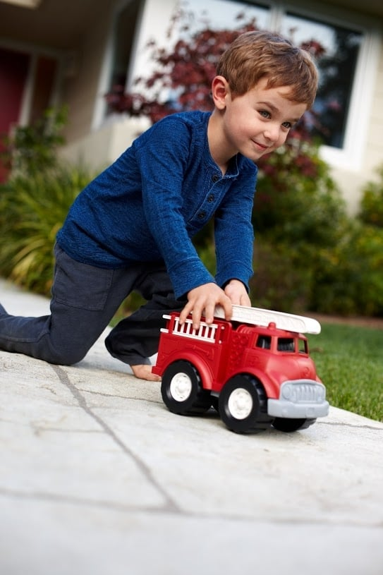 green toys fire truck lifestyle boy pushing toy outside on pavement
